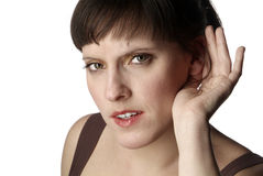 Listening woman. A young woman is holding one hand to her ear Stock Photography