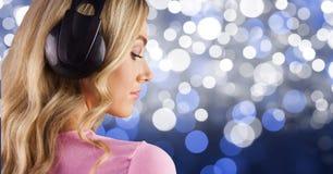 Listenning μουσική κοριτσιών ξανθών μαλλιών με τα ακουστικά πίσω στη φωτογραφία με το μπλε υπόβαθρο Στοκ φωτογραφία με δικαίωμα ελεύθερης χρήσης