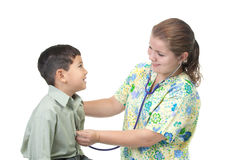 Listens to the heart beat. A nurse listens to the heart beat of a young boy royalty free stock image