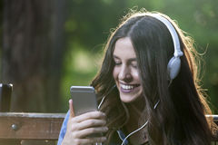 She listens to music and holds a mobile phone in her hand Stock Photo