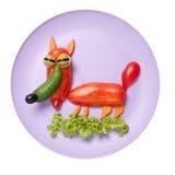 Listig räv som göras av nya grönsaker på lilaplattan Royaltyfri Bild