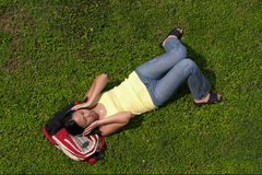 Listing to Music on Grass. Female Student Listing to Music on Grass Stock Photos