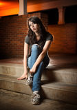 Listless girl sitting. On stone steps and looking at camera Stock Photography
