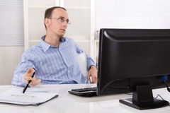 Listless sad and overworked business man sitting at desk with co. Listless and overworked business man sitting at desk with computer royalty free stock photography