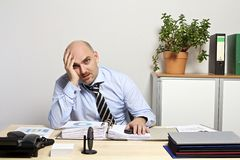 Listlessly affärsman på skrivbordet Arkivbild
