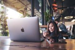Listopad 17th 2017: Azjatycka biznesowa kobieta trzyma mądrze telefon z laptopem na drewnianym stole w nowożytnej kawiarni, Chian Zdjęcie Royalty Free