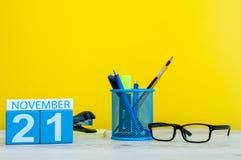 Listopadu 21st dzień 21 miesiąc, drewniany koloru kalendarz na żółtym tle z biurowymi dostawami Jesień czas Zdjęcia Stock