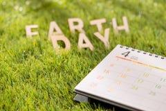 Listowy szczęśliwy ziemskiego dnia pojęcie z kalendarzem na zielonej trawie obraz stock