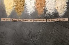 Listras de tipos e de etiquetas diferentes de farinha na tabela cinzenta, vista superior fotos de stock royalty free