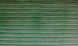 Listras horizontais velhas verdes de cortinas metálicas com borrões da oxidação e da pintura imagem de stock royalty free