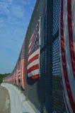 Listras verticais de bandeiras americanas no lado ensolarado da cerca da passagem superior da estrada Fotos de Stock Royalty Free