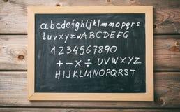 Listy i liczby na blackboard z ramą na drewnianym ściennym tle fotografia royalty free