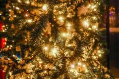 Lit acima da árvore de Natal fora na rua com luzes do círculo do bokeh na árvore e na distância - borrada imagem de stock royalty free