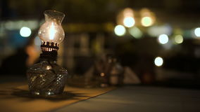 Lit antique oil lamp on table in cafe stock footage