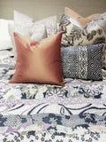 Lit avec un bon nombre d'oreillers colorés Photographie stock libre de droits