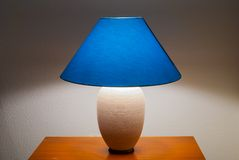 Lit bedside lamp over nightstand. Lamp on a nightstand with a blue glow on a textured wall-diffused lighting Stock Photography