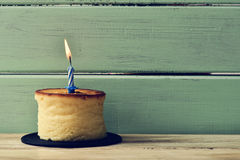 Lit birthday candle on a cheesecake Stock Photos