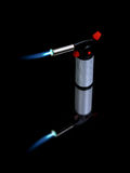 Lit blowtorch. Small handheld blowtorch with a blue flame Royalty Free Stock Photo
