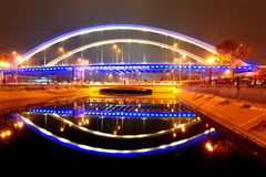 Lit bridge over river - urban symmetry Stock Photos
