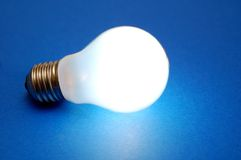Lit bulb on blue background Royalty Free Stock Photo