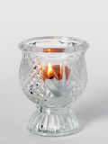 Lit Candle in Candleholder. On a white surface Royalty Free Stock Photography