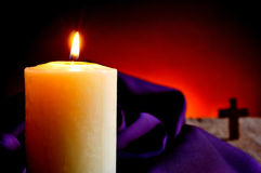 Lit candle and a Christian cross. Closeup of a lit candle with a purple drapery in the background and a Christian cross, on a wooden rustic surface and a red Royalty Free Stock Photography