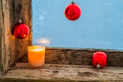 Lit candle and Christmas balls Royalty Free Stock Images