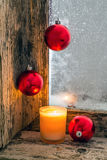 Lit candle and Christmas balls Royalty Free Stock Image