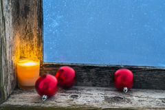 Lit candle and Christmas balls. On the windowsill of an old window with frosted glass. Copy space Stock Photos