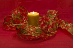 Lit candle and Christmas themed ribbon Royalty Free Stock Images