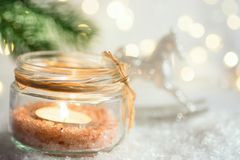 Lit candle in crystal jar candleholder hanging Christmas tree branch in snow ornament rocking horse in winter forest. New Year. Lit candle in crystal jar royalty free stock photos