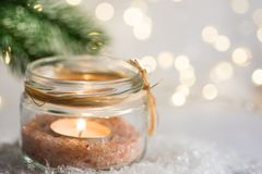 Lit candle in crystal jar candleholder hanging Christmas tree branch in snow in winter forest. New Year. Lit candle in crystal jar candleholder hanging Christmas stock photo