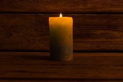 Lit candle in dark room. Lit pillar candle in dark room. Decoration and lighting. Warm and cozy atmosphere on winter days royalty free stock photo