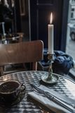 A lit candle on a dining table royalty free stock photo