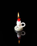 The lit candle and its reflection on black glass Royalty Free Stock Photo