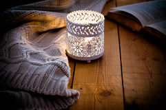 Lit candle in a lace candle holder, knitted sweater and an open book on wood background, cozy atmosphere. Selective focus Stock Image