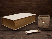Candle, matches and book on a wooden table. A lit candle, matches and a closed book lie on a wooden table stock photos