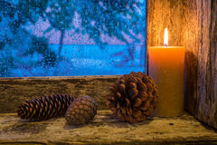 Lit candle and pine cones Royalty Free Stock Images