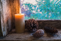 Lit candle and pine cones Stock Images