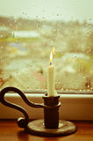 A lit candle on a rainy day Royalty Free Stock Images