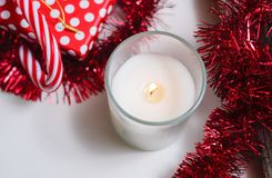 Lit candle and red Christmas decorations. Top view, copy space Stock Photo