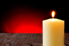 Lit candle on a rustic wooden table Royalty Free Stock Images