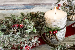 Lit candle and a stick of cranberries Royalty Free Stock Photos