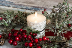 Lit candle and a stick of cranberries Stock Photos