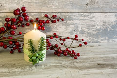 Lit candle and a stick with red berries Royalty Free Stock Images
