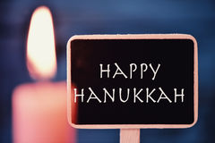Lit candle and text happy Hanukkah Stock Image