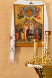 A lit candle and two candlesticks in front of an orthodoxal icon on the yellow background.  stock images