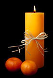 Lit candle with two clementines isolated on black. Lit candle with ribbon and two clementines isolated on black background Royalty Free Stock Photos