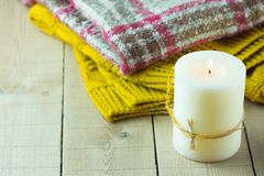 Lit Candle Yellow Knitted Sweater Checkered Plaid on Plank Wood Table by Window. Cozy Winter Autumn Evening. Natural Light Authentic Tranquil Atmosphere royalty free stock photography