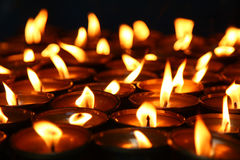 Lit candles. Lit asian transitional candles with a dark background Stock Photos